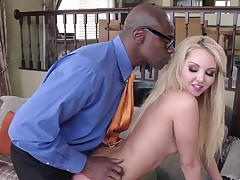 A golden-haired with long hair is sucking and riding a big black dick